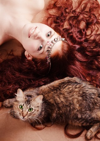 Young beautiful girl with long hair lying with a cat