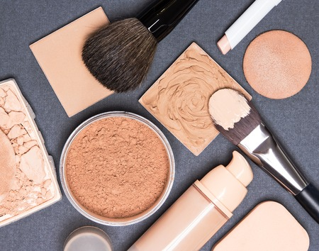 Photo pour Close-up of concealer pencil, corrector, open liquid foundation bottle and jar of loose powder, crushed compact powder, makeup brushes and cosmetic sponges on gray textured surface - image libre de droit