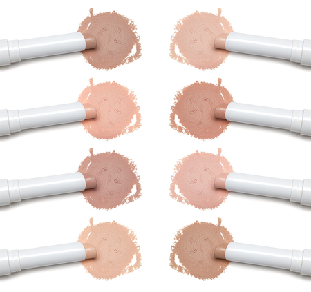 Close-up of various colors and shades of makeup concealer pencil on white background. Light and dark tones for different skin types