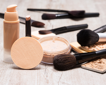 Photo pour Makeup products and accessories to even out skin tone and complexion. Round cosmetic sponge, bottle of liquid foundation, concealer pencil, jar of loose powder, makeup brushes on shabby wooden surface - image libre de droit