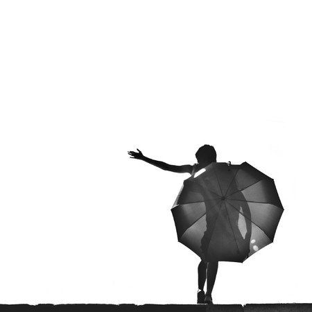 beautiful young woman with an umbrella against the sky