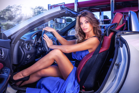 Photo for Sexy girl is shown with long blue dress sitting in white car cabriolet. - Royalty Free Image