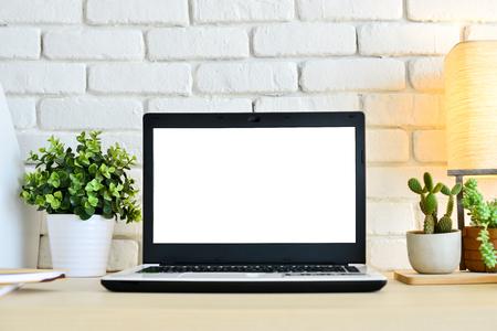 Foto de Laptop computer on wood desk with white brick wall background - Imagen libre de derechos