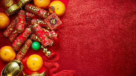 Foto de Chinese coins luck and firecrackers or chinese knot and Chinese gold ingots and Traditional (Foreign text means lucky blessing) and red envelopes and decoration with fresh oranges on red paper background  - Imagen libre de derechos