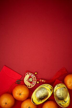 Foto de Chinese coins of luck or chinese knot and Chinese gold ingots and Traditional chinese knot  (Foreign text means blessing) and Red envelopes and decoration with Fresh oranges on Red Paper background - Imagen libre de derechos