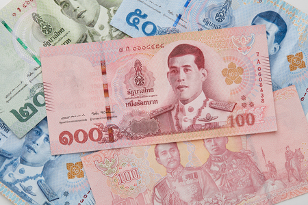 Foto de Close up 20 50 100 baht Hand Holding New Thai Baht Banknotes with The Image of King Rama X on White Background - Imagen libre de derechos