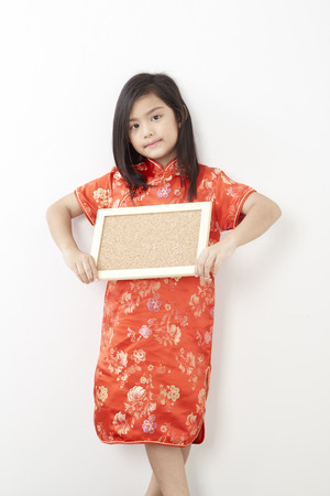Photo pour Girl child 8 years in chinese dress traditional cheongsam New year 2019 with holding a empty cork board - image libre de droit