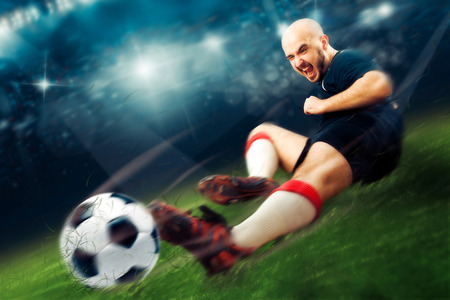 Photo pour football player in action makes a tackle in the game. Soccer game. Professional football player. Championship league. - image libre de droit