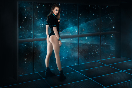 Photo pour sexual young girl with beautiful buttocks in uniform on spaceship board looking at the camera in space. fantastic picture of young beautiful girl on spaceship board in space. - image libre de droit