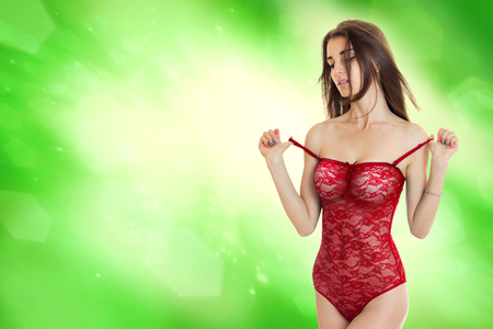 Photo for Sensual young girl take off a red body underwear in studio on green background - Royalty Free Image