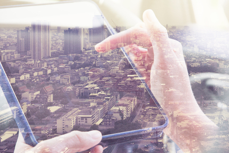 Foto de Using digital tablet double exposure and and cityscape background. Business  technology concept. - Imagen libre de derechos