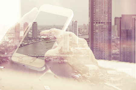 Foto de Double exposure image of people with smart phone and cityscape background,Business technology concept. - Imagen libre de derechos