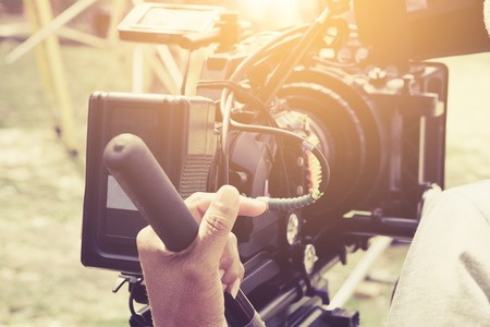 Photo for Cameraman with his video camera shooting, Hands Adjusting Camera,film production crew, behind the scenes background. - Royalty Free Image