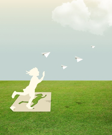 Foto de Paper cut of child on green grass dream concept - Imagen libre de derechos