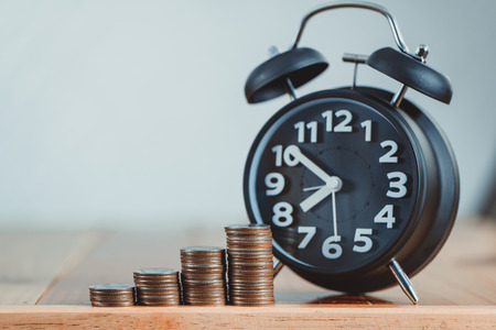 Foto de Alarm clock and step of coins stacks on working table, time for savings money concept, banking and business idea. vintage tone. - Imagen libre de derechos