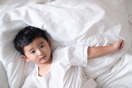 Photo for 3 years old little sick or illness Asian boy at home on the bed, sad kid laying resting on white bed with pillow and blanket, top view with copy space for add text. - Royalty Free Image
