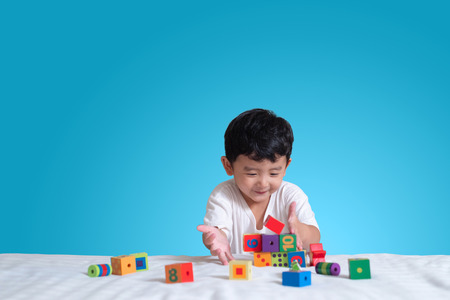 Foto de 3 years old little cute Asian boy play toy or square block puzzle at home on the bed, kid lying learn by playing block shape or pieces, education and healthy concept. - Imagen libre de derechos