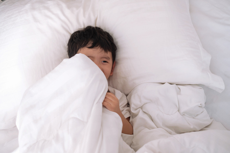 Foto de 3 years old little cute Asian boy in white shirt at home on the bed, kid lying playing and smiling on white bed with pillow and blanket, top view with copy space for add text. - Imagen libre de derechos