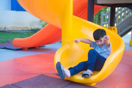 Foto de Asian kid playing slide at the playground under the sunlight in summer, Happy kid in kindergarten or preschool school yard. - Imagen libre de derechos