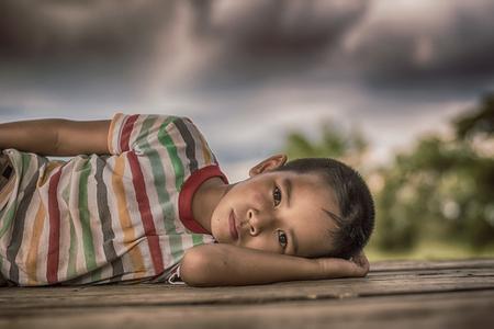 Foto de Little boy unhappy sleeping alone on abandoned temporary housing. - Imagen libre de derechos