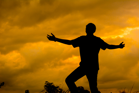Photo pour Silhouette man praying with hand up to God. Sunset background. - image libre de droit