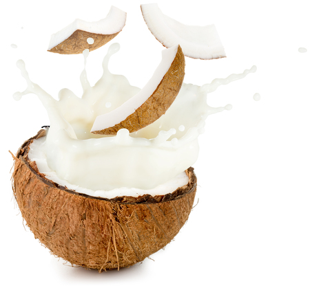 Photo for coconut milk and pieces spilling out half nut - Royalty Free Image