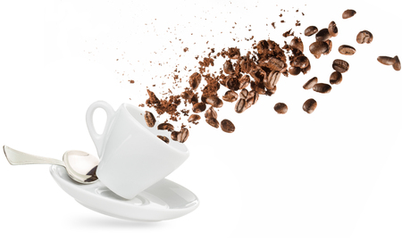 Foto de coffee beans and powder spilling out of a cup isolated on white - Imagen libre de derechos