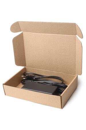 Foto de Laptop charger in cardboard box on white background - Imagen libre de derechos