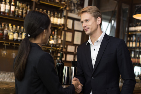 Man Agree for Working with woman at Bar. people shake hand together for business concept. Business team handshake concept.