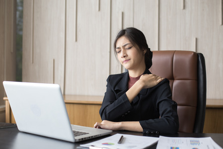 Foto de Asian woman working  hard and feeling dizzy at office, woman with office syndrome concept - Imagen libre de derechos