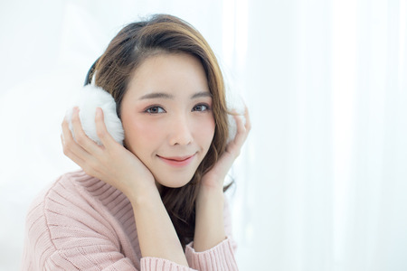 Photo pour Attractive Asian Girl wearing sweater listen music with smile at home. Woman with winter concept. - image libre de droit