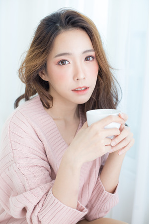 Photo for Asian Woman holding coffee cup at bedroom. People lifestyle concept. - Royalty Free Image