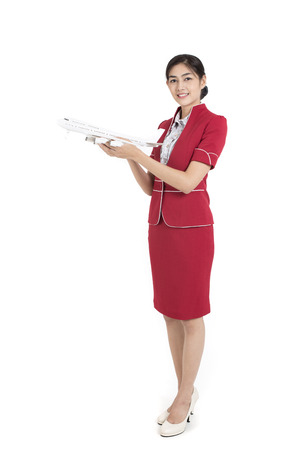 Foto de Portrait of Asian Air Hostess holding airplane model and passport, stand and smile at isolated on white background - Imagen libre de derechos