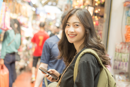 Photo pour Portrait of Happy Traveler Woman in market. Asian women Using Smartphone for seach Location. Woman with Travel Concept. - image libre de droit