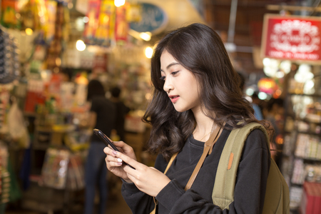 Foto per Portrait of Happy Traveler Woman in market. Asian women Using Smartphone for seach Location. Woman with Travel Concept. - Immagine Royalty Free