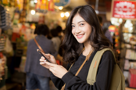 Photo for Portrait of Happy Traveler Woman in market. Asian women Using Smartphone for seach Location. Woman with Travel Concept. - Royalty Free Image