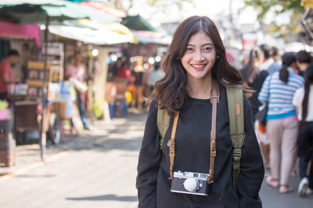 Photo pour Portrait of Happy Traveler Woman in Market. Asian women Hold Retro Camera for Take Photo, People with Happy emotions. - image libre de droit