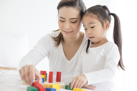 Photo pour Mam playing toy with her Daugther at home. Happy Family Concept. - image libre de droit