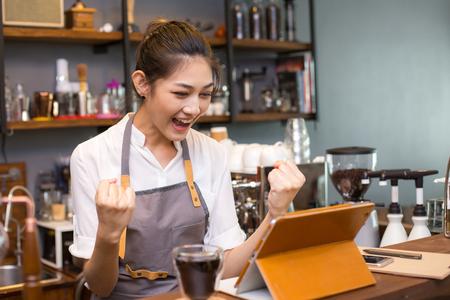 Foto de Asian barista woman using tablet for promote shop. Woman success for online marketing. - Imagen libre de derechos