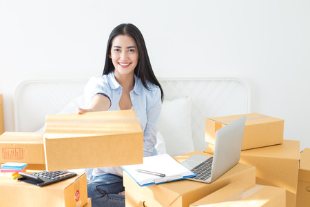 Photo pour Young asian woman business owner work and white down address for deliver at home, woman business owner concept, 20-25 year old. - image libre de droit