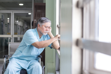 Foto de Asian old man sit on wheelchair looking out to other place. People with health care and medical concept. - Imagen libre de derechos