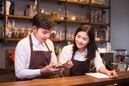Foto de Asian couple barista  working in coffee shop counter.  Barista working at cafe. People working with small business owner or sme concept. - Imagen libre de derechos