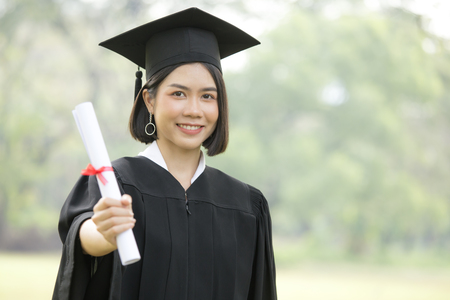 Photo for Young Asian Woman Students wearing Graduation hat and gown, Garden background, Woman with Graduation Concept. - Royalty Free Image