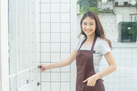 Foto de Asian Women Barista smiling and looking to camera in coffee shop counter. Barista female working at cafe. Working woman small business owner or sme concept. Vintage tone. - Imagen libre de derechos