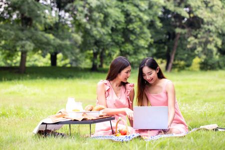 Photo pour Female and friend picnic together at the public garden, Women resting at garden together in holiday. People with lifestyle, relax, holiday concept. - image libre de droit