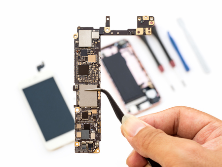 Foto de Close-up of technician hand clamping smartphone logic board on blurred smartphone component background - Imagen libre de derechos