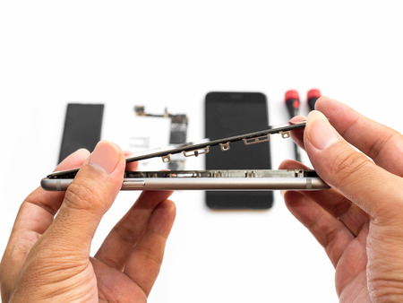 Foto de Close-up of technician hand taking off cracked smartphone screen on blurred smartphone component background - Imagen libre de derechos
