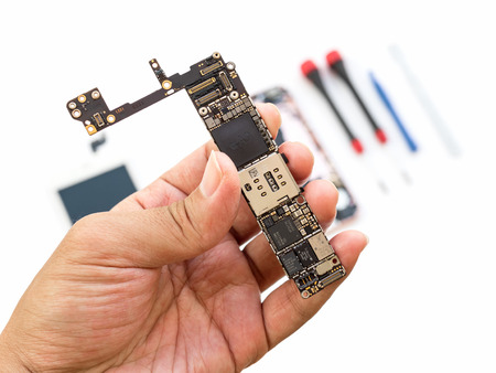 Foto de Chiangrai, Thailand: September 13, 2017 - Close-up image of technician hand showing Apple iPhone 6S logic board on blurred components and tools background.  - Imagen libre de derechos