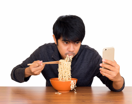 Photo pour Man eating chinese noodle monstrously whilst looking and using smartphone isolate on white background with clipping path. Concept of smartphone addiction, phubbing or social network issues - image libre de droit