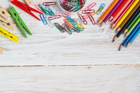 Photo for Desk of an artist, colorful pencils  and paperclips on the white wooden table background - Royalty Free Image